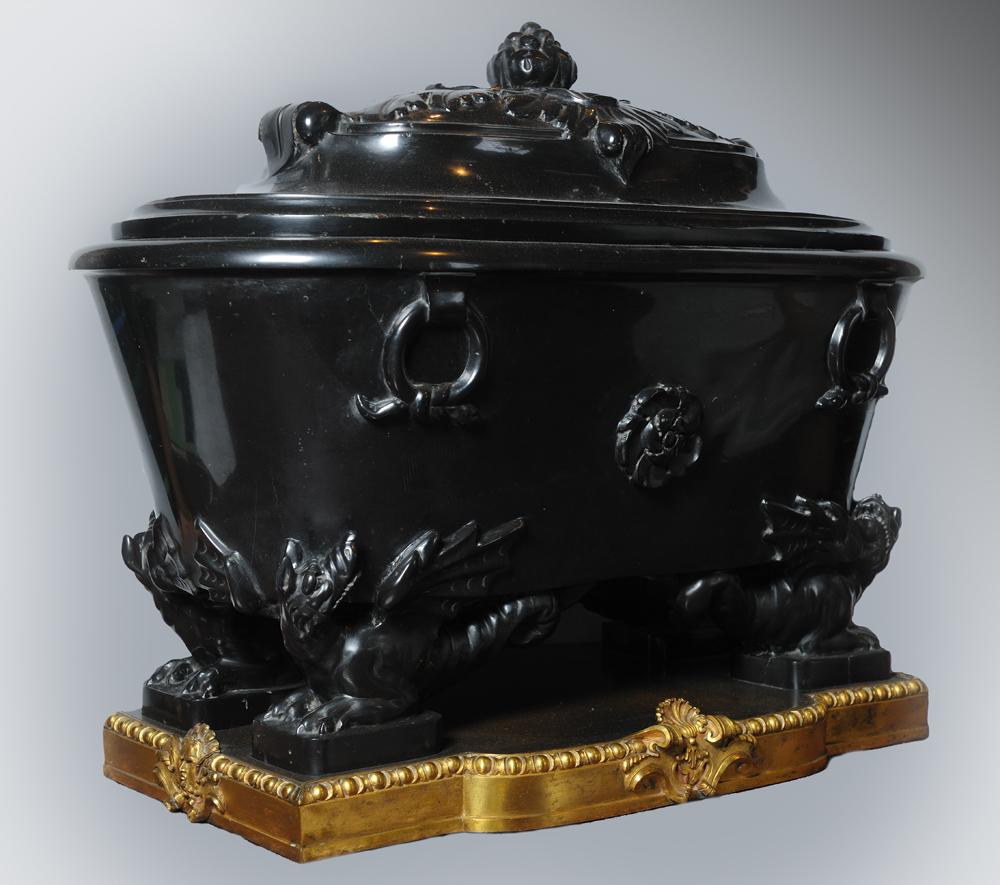 Urna in nero antico poggiante su draghi con zoccolo di metallo dorato